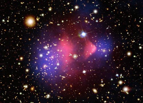 """Esta imagen compuesta muestra el cúmulo de galaxias 1E 065756, formado después de la colisión de dos grandes conglomerados de galaxias. El gas caliente detectado por el telescopio de rayos X """"Chandra"""", representado por el color rosado, contiene la mayor parte de la materia ordinaria. Las regiones en azul muestran donde debería estar la mayor parte de la masa según efectos gravitacionales (usando la técnica de los lentes gravitacionales). La mayoría de la materia, en el lado azulado, está claramente separada de la ordinaria (región rosada) y no es observable directamente. La mejor explicación de la que se dispone es que allí hay Materia Oscura. Imagen cortesía: Colaboración Chandra, Universidad de Harvard."""